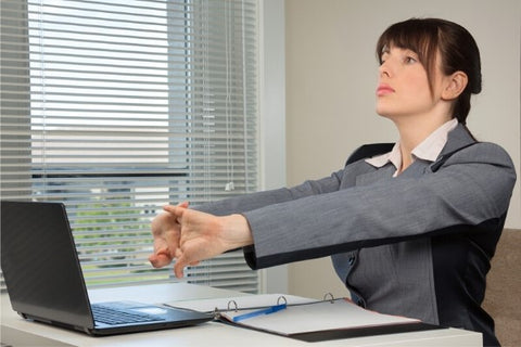 Photo of a woman doing an exercise for the carpal tunnel at the workplace
