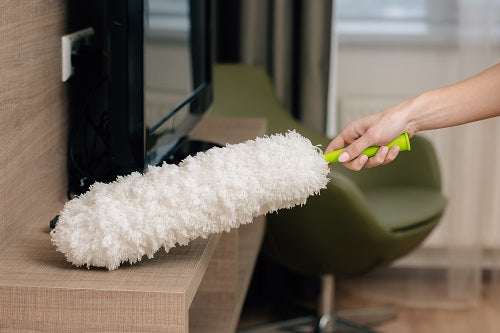 Cleaning a wood tabletop with a feather duster