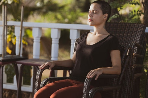 Photo of a woman sitting on a chair and doing meditation