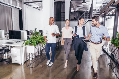 Photo of young smiling multiethnic business colleagues walking together in an office