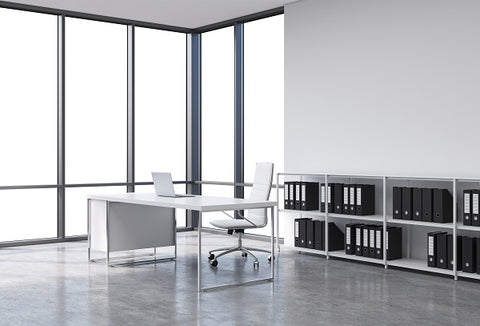 Photo of a workplace in a modern panoramic office. A white desk with a laptop, white leather chair and a bookshelf with black document folders.