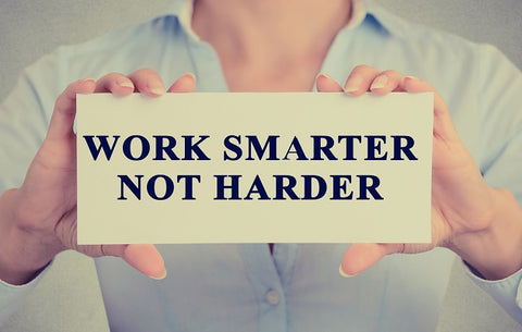 "The image of businesswoman's hands holding the card with motivational message phrase text written on it ""Work Smarter Not Harder"""