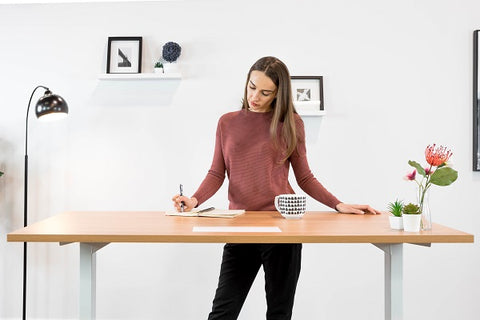 Photo of a woman working for standing desk