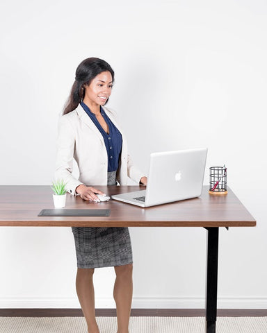 Photo of a businesswoman with a laptop at a standing desk