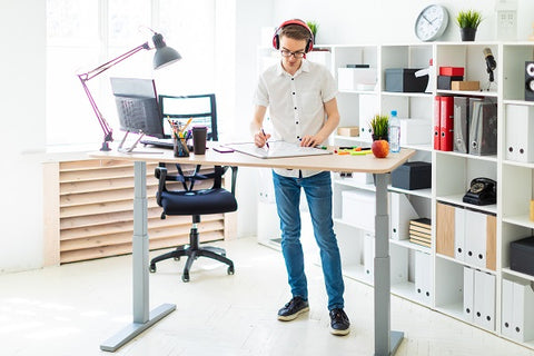 Photo of a young man in headphone he is working with documents for a standing desk