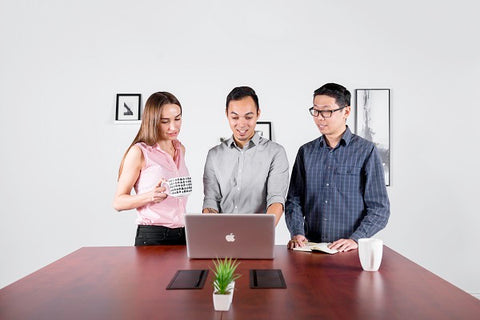 Photo of young people talking at standing desk