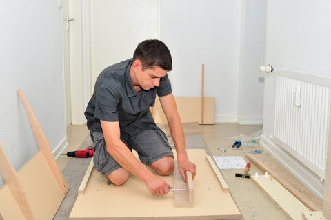 Photo of a man mounting furniture with a screwdriver