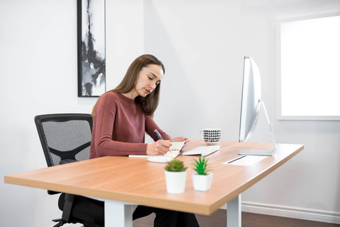 Girl sitting with a laptop at a standing desk