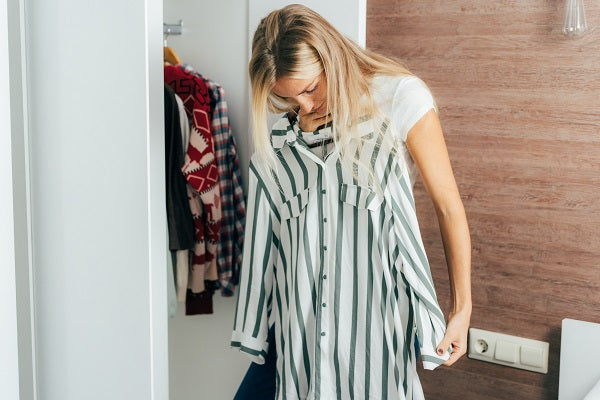 A woman chooses what to wear in her wardrobe tries