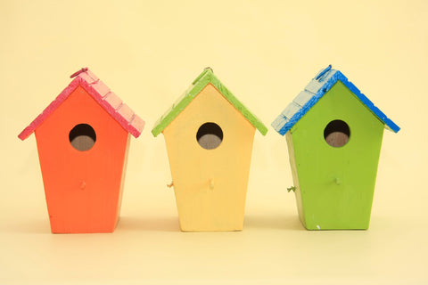 Photo of three birdhouses on a yellow background