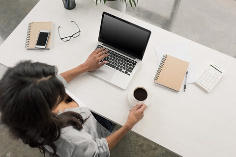 Photo of a woman working on laptop and drinking coffee