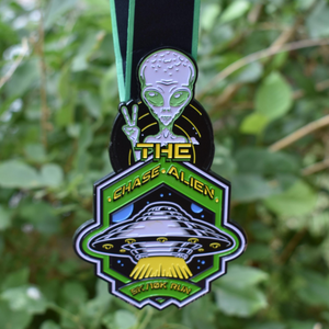 Virtual Run Chase The Alien 5K 10K run medal with glow in the dark space alien from Area 51 forest background