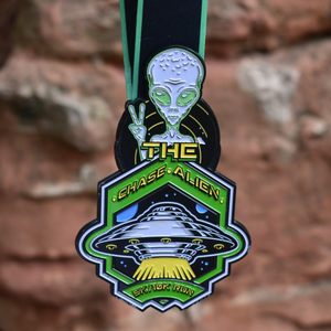 Virtual Run Chase The Alien 5K and 10K finisher medal with alien giving the peace sign with logo ribbon to go around neck