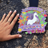 Woman's hand next to Chase The Unicorn 5K virtual run finisher medal to show just how big the medal is