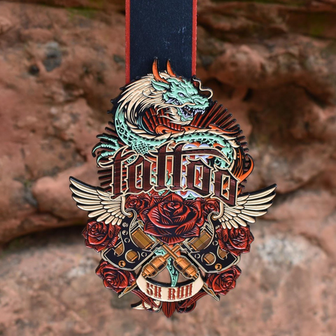 Image of Tattoo 5K virtual run medal featuring tattoo artist ink style art with roses, wings, a dragon, and tattoo guns in front of red rocks