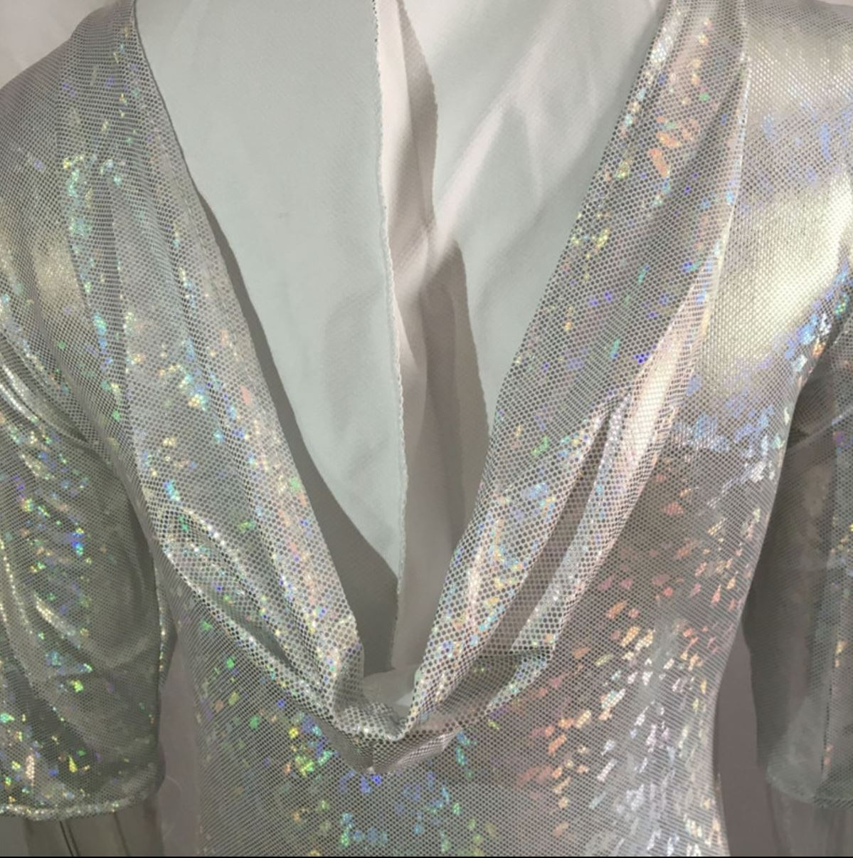 Holographic white in colour, bodysuit with 3/4 sleeves and hoodie attached. Festival wear. Pas de bourree dancewear. Pasdebourreedancewear.