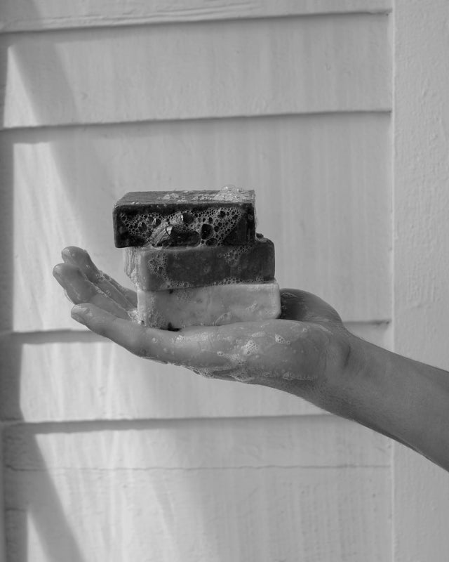 Hand Holding Organic Soap with Bubbles Shadows