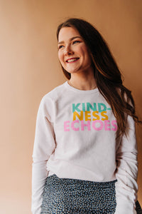woman wearing Ramble and Company's kindness echoes soft comfortable inspirational graphic raglan sweatshirt in petal pink