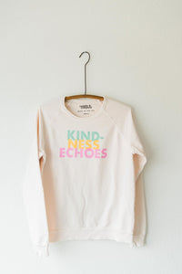 Ramble and Company's kindness echoes soft comfortable inspirational graphic raglan sweatshirt in petal pink front view hanging