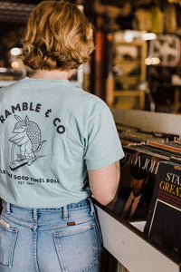 woman wearing Ramble and Company's let the good times roll armadillo on scooter vintage slim fit unisex soft comfortable inspirational graphic t-shirt  in harbor gray light blue color back view
