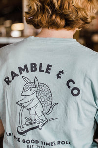 woman wearing Ramble and Company's let the good times roll armadillo on scooter vintage slim fit unisex soft comfortable inspirational graphic t-shirt  in harbor gray light blue color close up back view