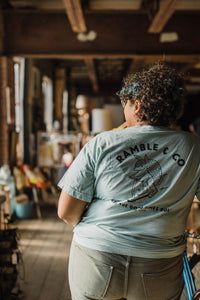 curvy woman wearing Ramble and Company's let the good times roll armadillo on scooter vintage slim fit unisex soft comfortable inspirational graphic t-shirt  in harbor gray light blue color close up back view