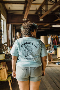 curvy woman wearing Ramble and Company's let the good times roll armadillo on scooter vintage slim fit unisex soft comfortable inspirational graphic t-shirt  in harbor gray light blue color full body back view