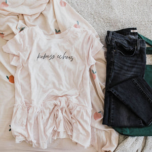 flat lay of Ramble and Company's kindness echoes ladies swing top soft comfortable t-shirt with peplum waist in petal pink