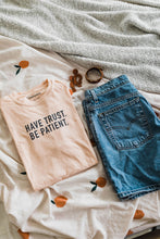 Load image into Gallery viewer, Ramble and Company's have trust be patient unisex soft comfortable inspirational graphic t-shirt in apricot flat lay