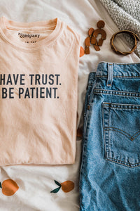 Ramble and Company's have trust be patient unisex soft comfortable inspirational graphic t-shirt in apricot flat lay
