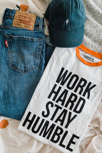 Ramble and Company's work hard stay humble white ringer unisex soft comfortable inspirational graphic t-shirt in vermillion orange flat lay
