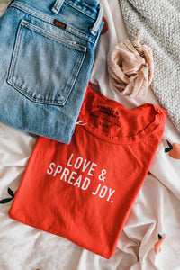 Ramble and Company's love and spread joy women's soft comfortable inspirational graphic t-shirt in fiesta flat lay