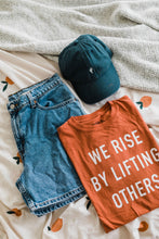 Load image into Gallery viewer, Ramble and Company's we rise by lifting others unisex soft comfortable inspirational graphic t-shirt in ginger spice flat lay