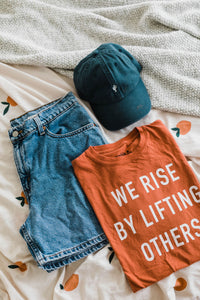 Ramble and Company's we rise by lifting others unisex soft comfortable inspirational graphic t-shirt in ginger spice flat lay