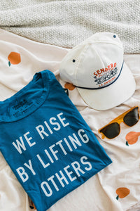 Ramble and Company's we rise by lifting others women's soft comfortable inspirational graphic t-shirt in mykonos blue flat lay