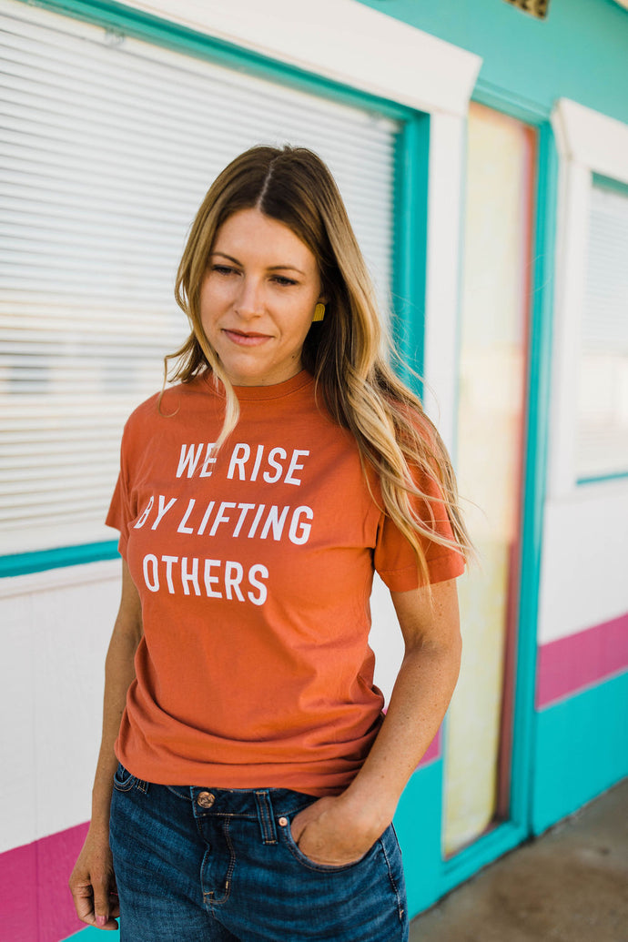 woman wearing Ramble and Company's we rise by lifting others unisex soft comfortable inspirational graphic t-shirt in ginger spice front view close up