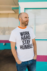 man wearing Ramble and Company's work hard stay humble white ringer unisex soft comfortable inspirational graphic t-shirt in vermillion orange front view close up