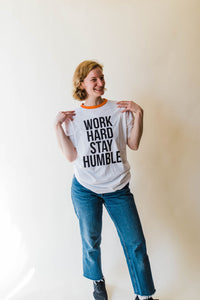 woman wearing Ramble and Company's work hard stay humble white ringer unisex soft comfortable inspirational graphic t-shirt in vermillion orange front view full body