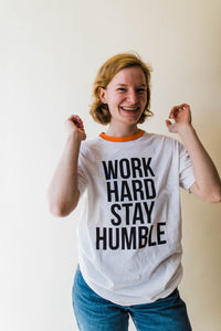 woman wearing Ramble and Company's work hard stay humble white ringer unisex soft comfortable inspirational graphic t-shirt in vermillion orange front view close up