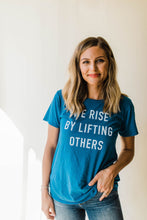 Load image into Gallery viewer, woman wearing Ramble and Company's we rise by lifting others women's soft comfortable inspirational graphic t-shirt in mykonos blue front view close up