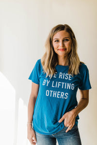 woman wearing Ramble and Company's we rise by lifting others women's soft comfortable inspirational graphic t-shirt in mykonos blue front view close up