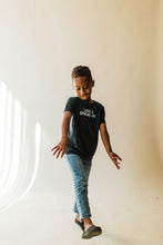 Load image into Gallery viewer, kid wearing Ramble and Company's love and spread joy kids soft comfortable inspirational graphic t-shirt in pirate black front view full body