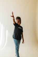 Load image into Gallery viewer, kid wearing Ramble and Company's love and spread joy kids soft comfortable inspirational graphic t-shirt in pirate black side view