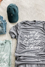 we rise by lifting others tee by Ramble & Company || shop now at rambleandcompany.com or visit our storefront in downtown Wichita Falls, Texas || soft inspirational graphic t-shirts