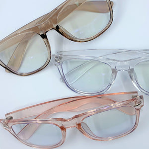Blue light filtering glasses, shown in clear, champagne and pink pastel translucent frames.