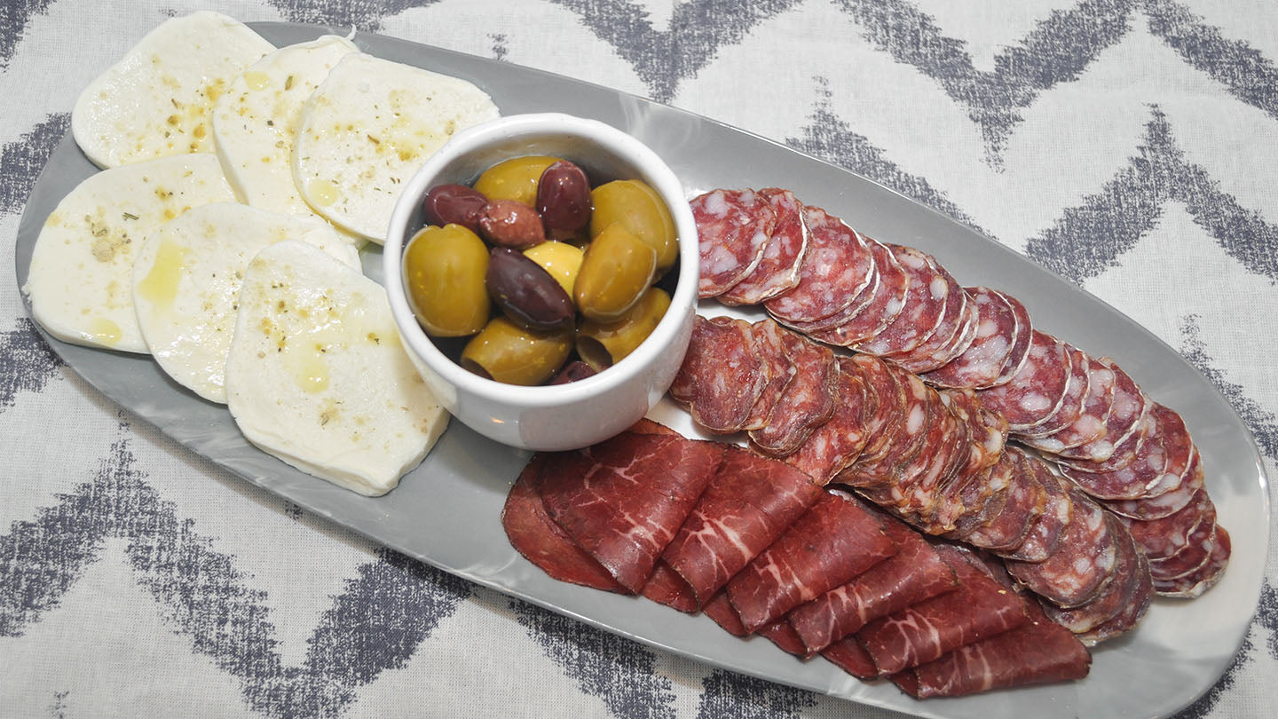 Antipasto of mozzarella, olives, and cured Italian sausages.