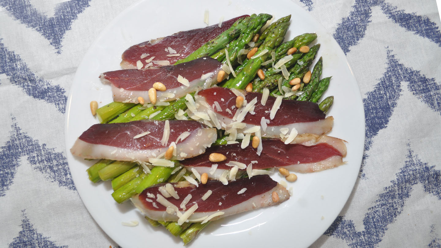 Roasted asparagus on a plate with duck breast prosciutto.