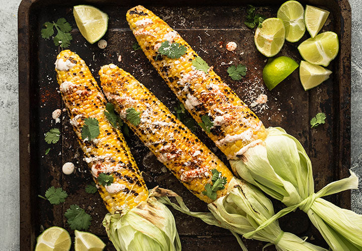 Grilled corn on the cob served with lime and cheese.