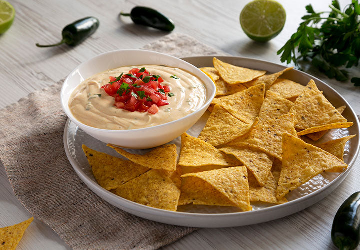 Queso dip served in a bowl with torilla chips.