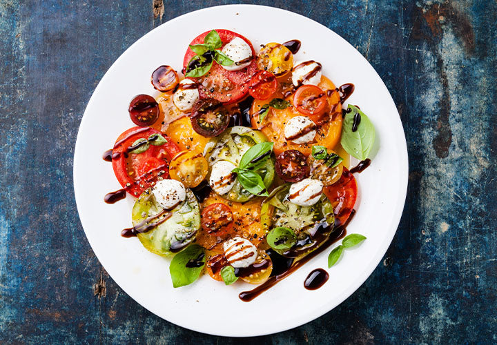 Tomato salad with fresh mozzarella cheese, basil leaves, and balsamic vinaigrette.